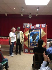 John Tignor and Dianna Kimpel, who made a quilt for Tignor, pose at a military appreciation ceremony earlier this month.