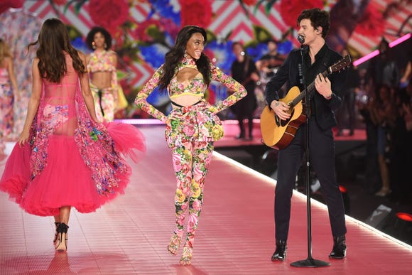 Winnie Harlow, center, walks the runway as Shawn Mendes performs during the 2018 Victoria's Secret Fashion Show.