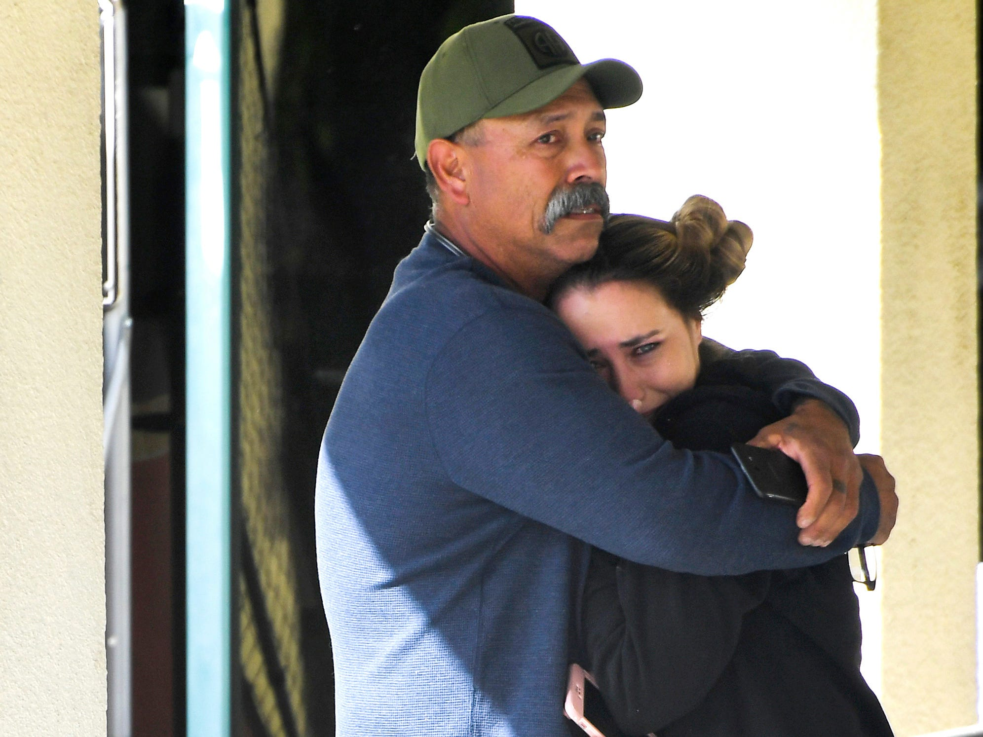 A woman is comforted outside of a family assistance and reunification center in Thousand Oaks, Calif.