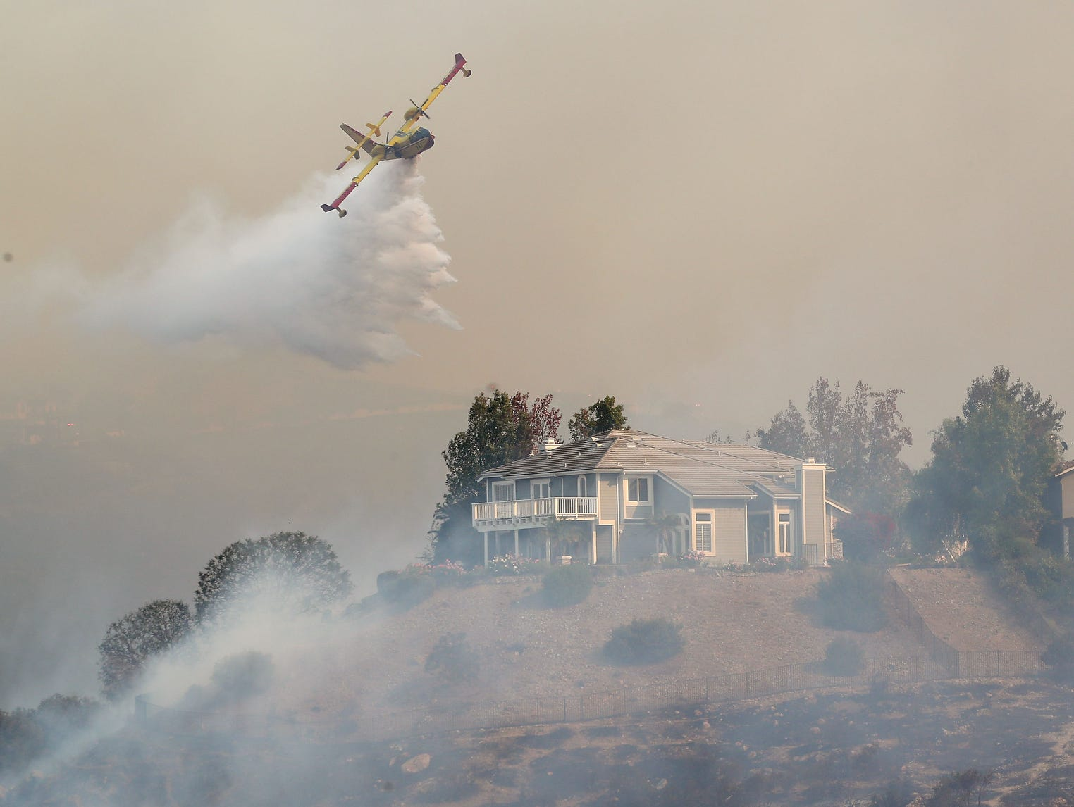 A firefighting air tanker is used to fight the Woolsey Fire as it threatens hillside homes in Westlake Village.