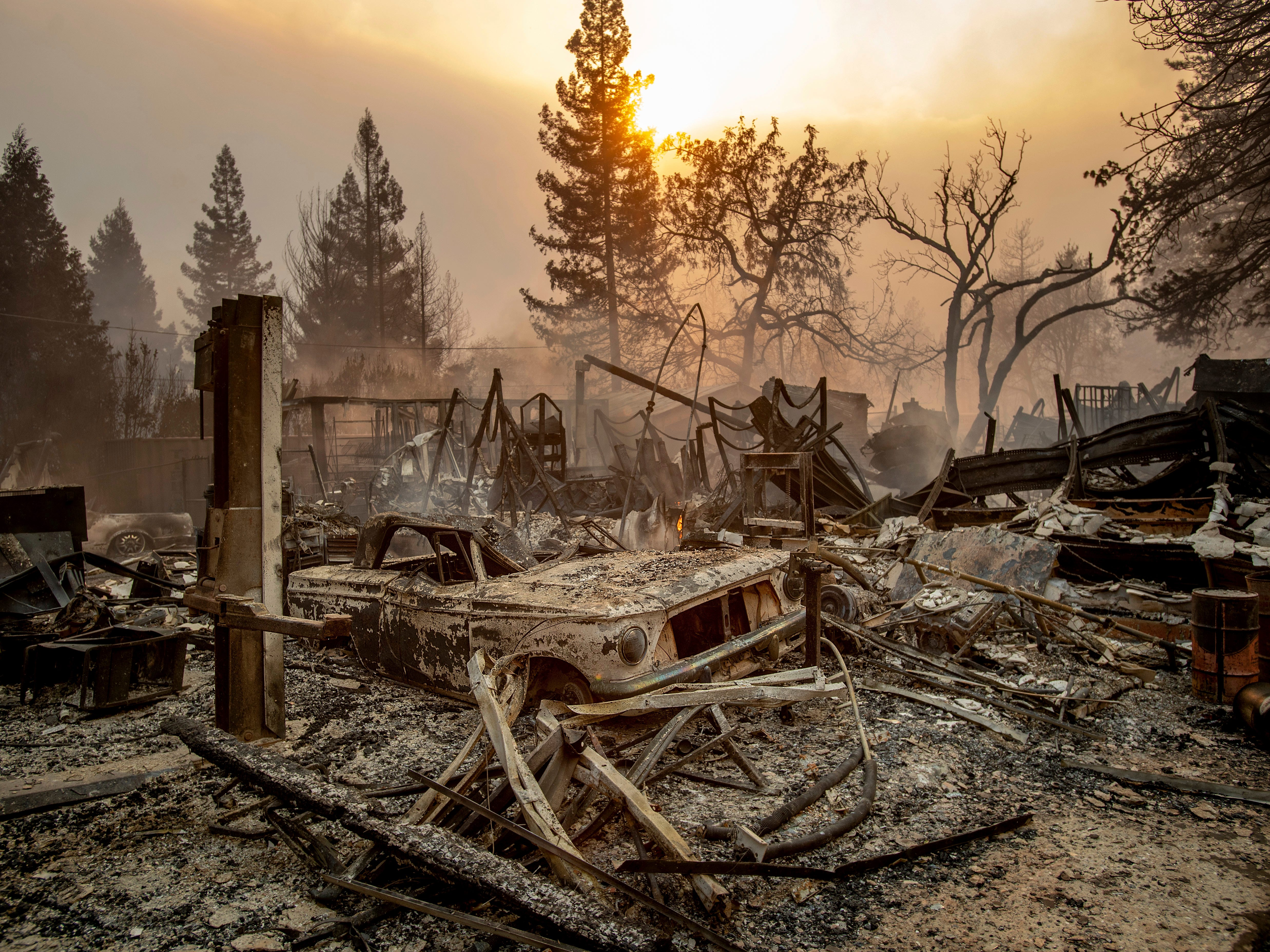 A vintage car rests among debris as the Camp Fire tears through Paradise, Calif., on  Nov. 8, 2018.