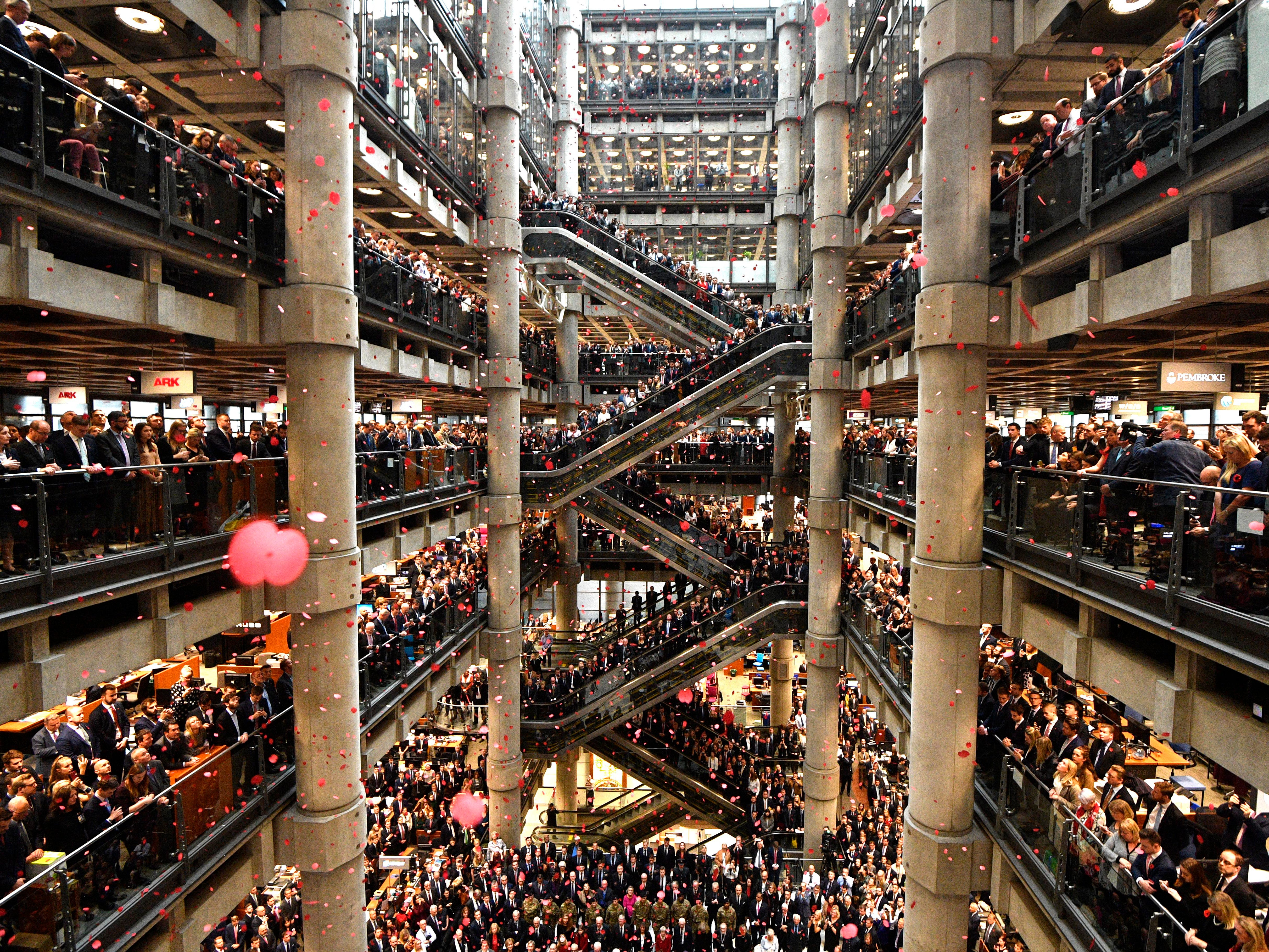 epa07153022 Staff line the atrium as poppies fall during a Armistice commemoration service at Lloyds of London, in the City of London, Britain, 09 November 2018. The 11 November 2018 marks the 100th anniversary of the First World War Armistice with services taking place across the world to commemorate the occasion.  EPA-EFE/NEIL HALL ORG XMIT: NGH01