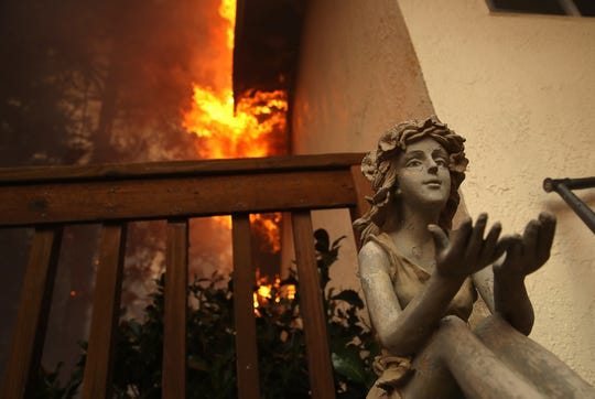 A statue sits on the deck of a burning home as the Camp Fire moves through the area on November 8, 2018 in Paradise, California. Fueled by high winds and low humidity, the rapidly spreading Camp Fire has ripped through the town of Paradise and has quickly charred 18,000 acres and has destroyed dozens of homes in a matter of hours. The fire is currently at zero containment.