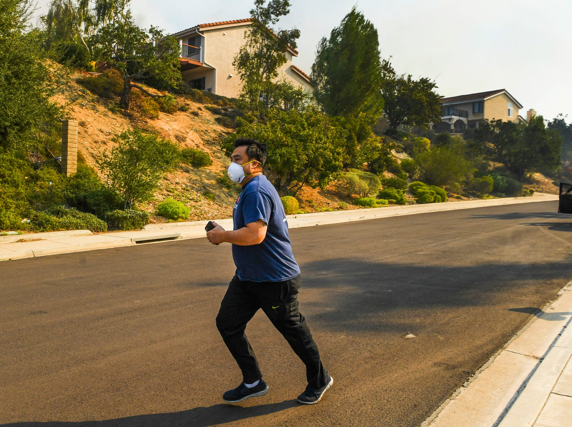 A resident wearing a breathing mask runs down Shadow Oaks Place in Thousand Oaks, Calif., as smoke from flames in a hill above the homes fills the neighborhood. Some residents decided to leave their homes as firefighters kept a watchful eye on the fire.
