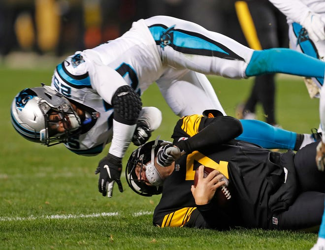 Ben Roethlisberger is hit by Panthers safety Eric Reid as he slides at the end of a run.