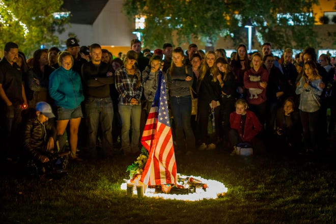 People gather around candles and a U.S. flag during a vigil to pay tribute to the victims of a shooting in Thousand Oaks on Thursday.