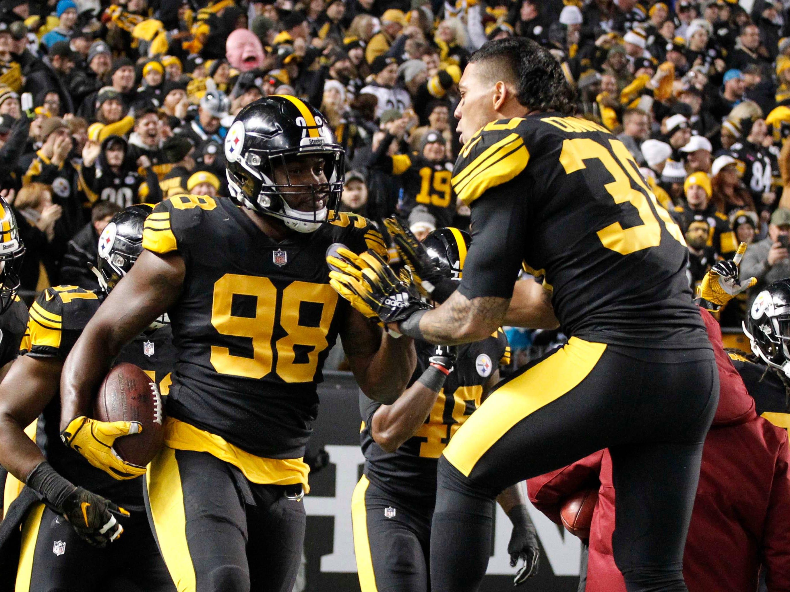 Pittsburgh Steelers running back James Conner congratulates inside linebacker Vince Williams (98) on his touchdown against the Carolina Panthers during the first quarter at Heinz Field.