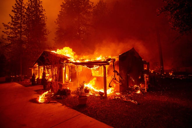 A home burns during the Camp fire in Paradise, California on November 08, 2018. - More than 18,000 acres have been scorched in a matter of hours burning with it a hospital, a gas station and dozens of homes.