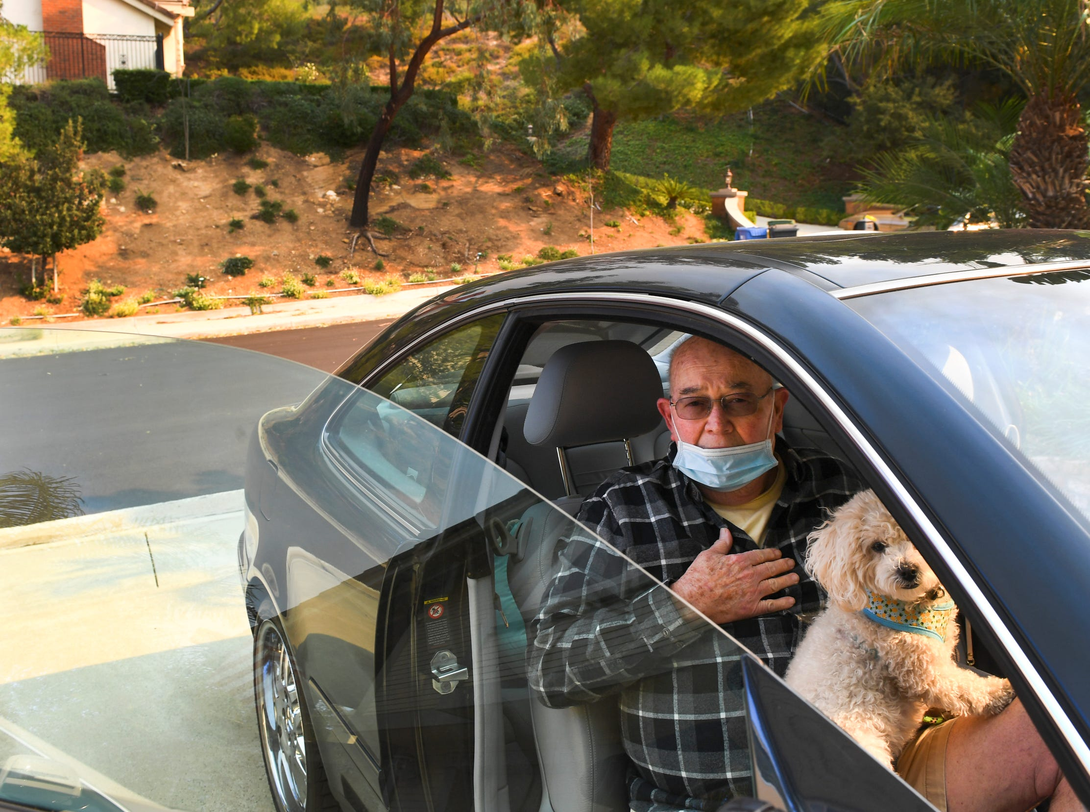 Jeff Riley waits to be evacuated from his home on Shadow Oaks Place, in Thousand Oaks, Calif., with the family dog.  Flames on a hill above the neighborhood caused residents to leave their homes.