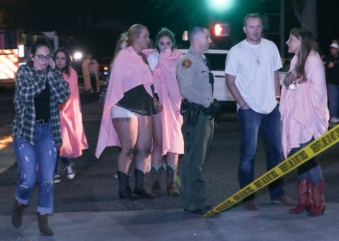 People comfort each other at the scene of a mass shooting at the Borderline Bar and Grill in Thousand Oaks, California.