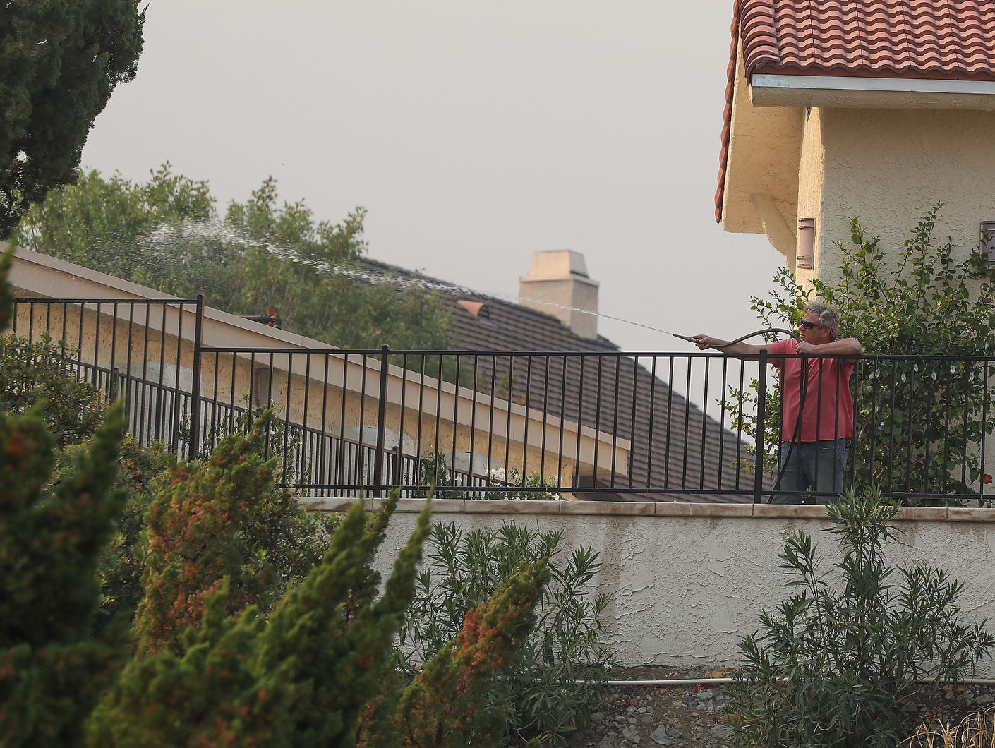 A man tries to prevent fire from reaching his Westlake Village, Calif. home.