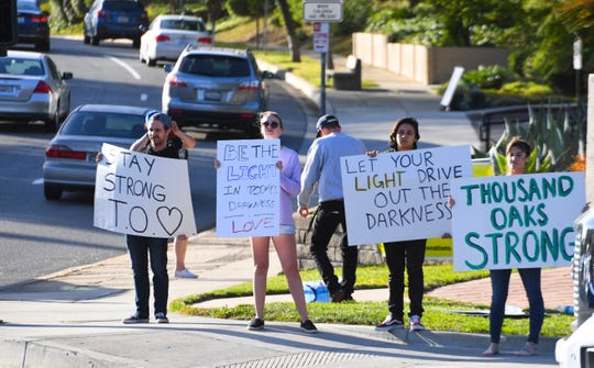 Signs of support greet motorists at a busy intersection in Thousand Oaks, Calif. on Nov. 8, 2018.