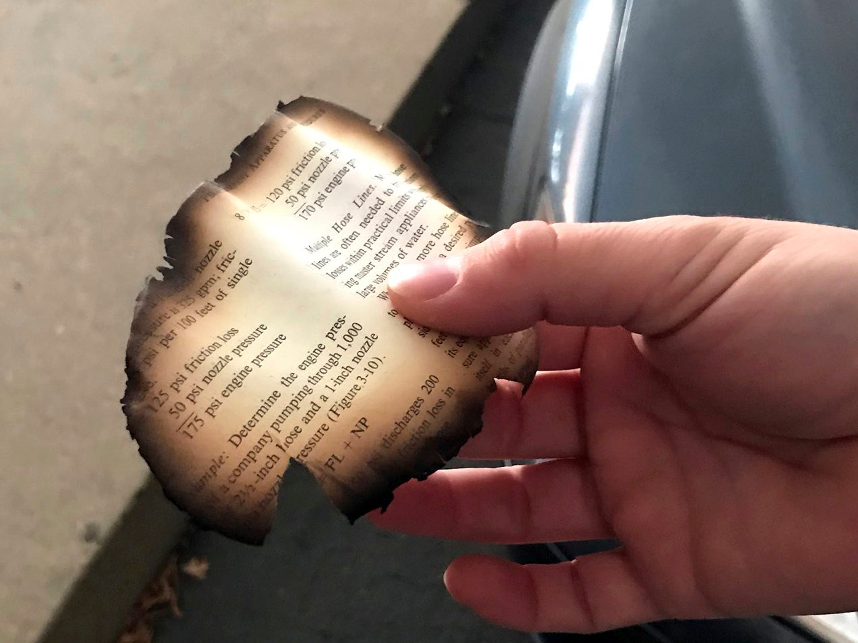A piece of a burned page that fell out of the sky in Chico, Calif. on Nov. 8, 2018, as the Camp Fire burns nearby.