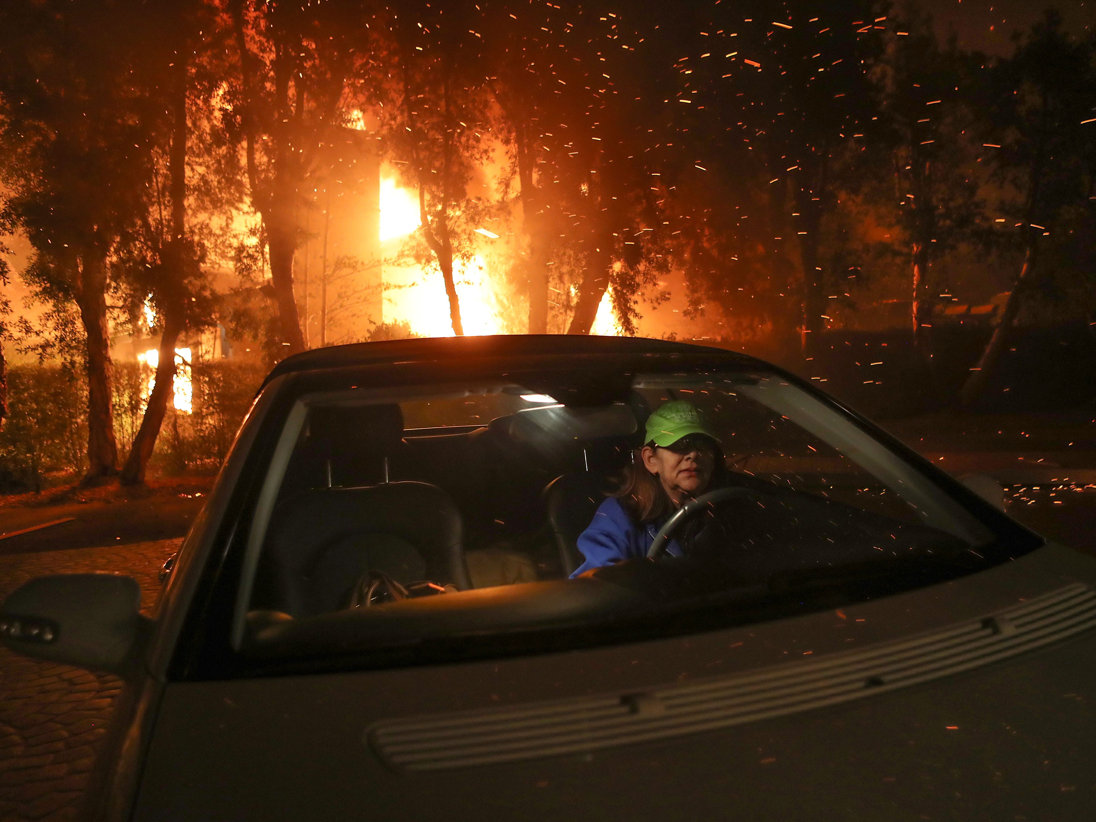 Tina Weeks jumps into her car to evacuate after her neighbors house became fully engulfed by the Woolsey Fire in Oak Park, Ca., in the early morning of November 9, 2018. (Via OlyDrop)