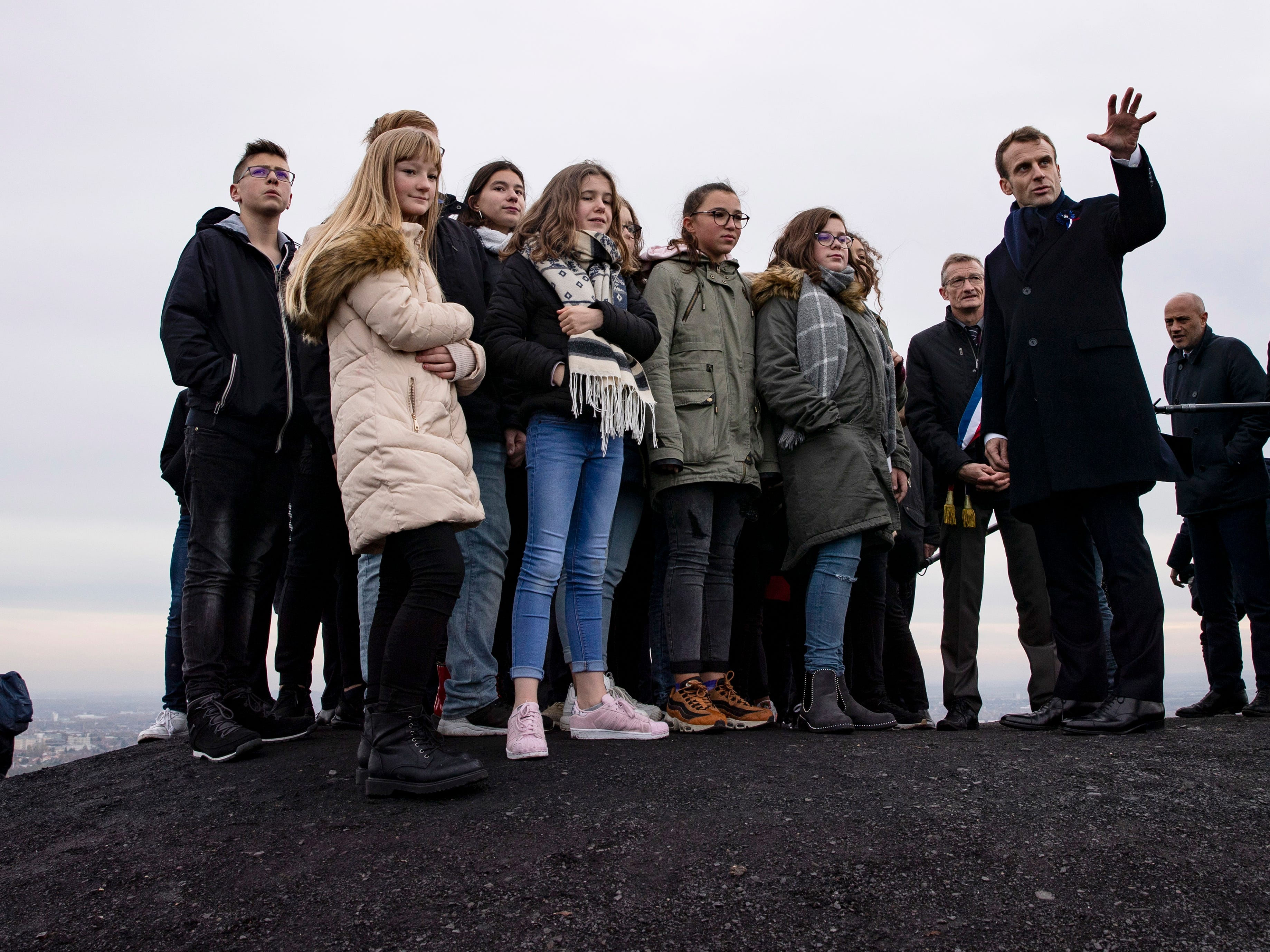 epa07153055 French President Emmanuel Macron (R) visits with young people and officials the slag heaps aka 'terrils' in Loos en Gohelle, near Lens, France, 09 November 2018. Macron is currently on a six-day tour to visit the most iconic landmarks of the First World War ahead of the commemorations of the 100th anniversary of the 11 November 1918 armistice. Lens an important industrial center with coal mining begining at 1849 with the last coal mine in Lens closed in 1986. The Canadian National Vimy Memorial dedicated to the Battle of Vimy Ridge in WWI is located nine kilometers outside Lens.  EPA-EFE/ETIENNE LAURENT / POOL ORG XMIT: ELA69