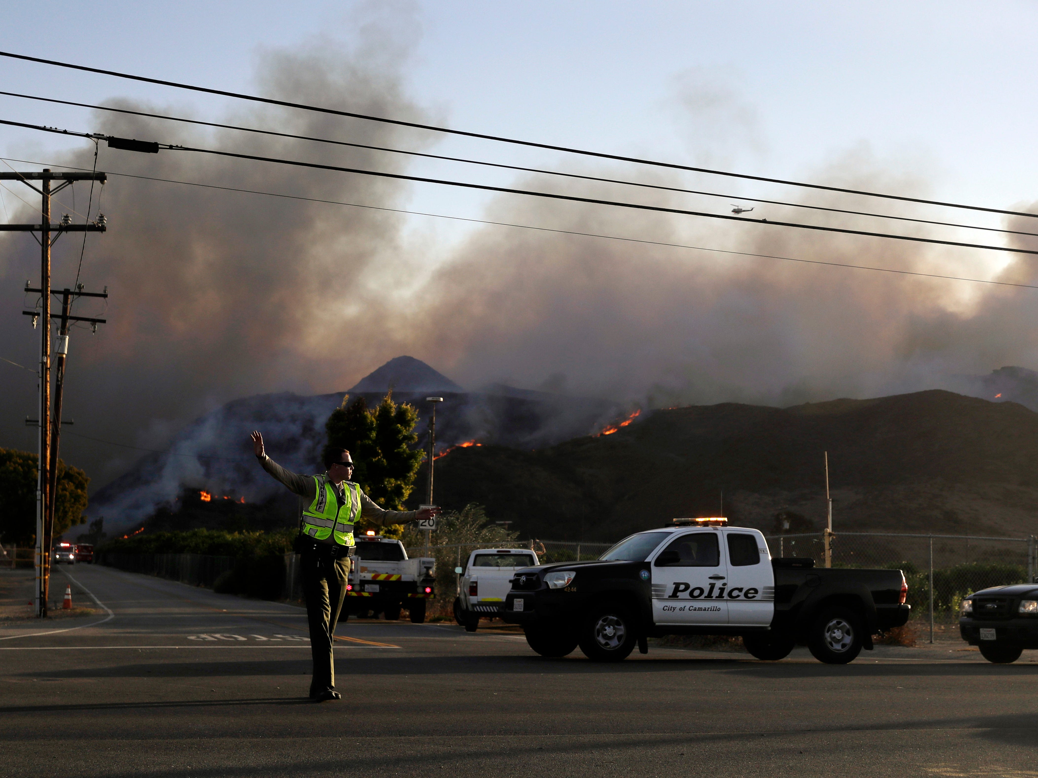 A police officer mans a checkpoint in front of an advancing wildfire on Nov. 8, 2018, near Newbury Park, Calif.