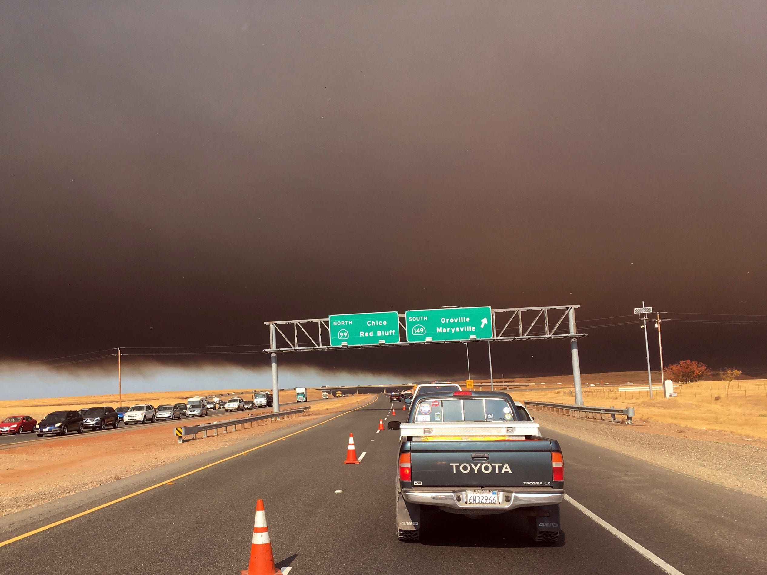 Smoke from the Camp Fire, burning in the Feather River Canyon near Paradise, Calif., darkens the sky as seen from Highway 99 near Marysville, Calif. on Nov. 8, 2018.