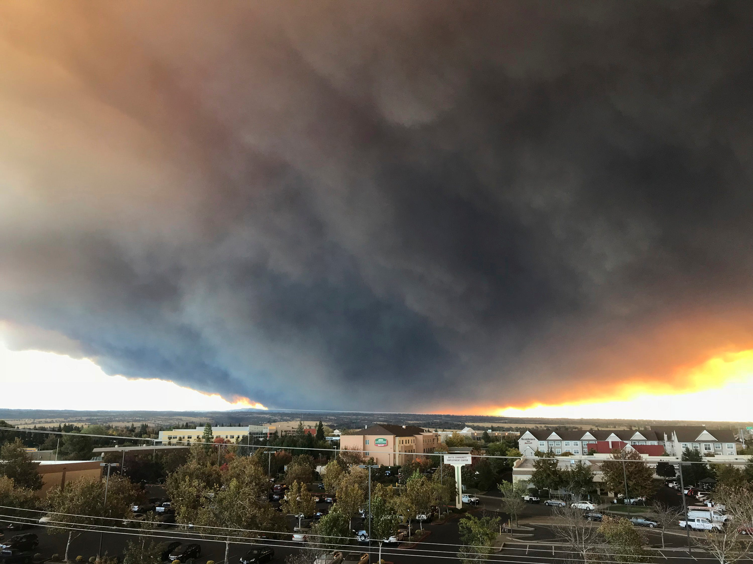 The massive plume from the Camp Fire, burning in the Feather River Canyon near Paradise, Calif., wafts over the Sacramento Valley as seen from Chico, Calif., on Nov. 8, 2018.