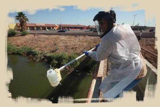 Un empleado de la Junta Regional de Control de Calidad del Agua de California toma una muestra de agua del New River en Calexico, California.