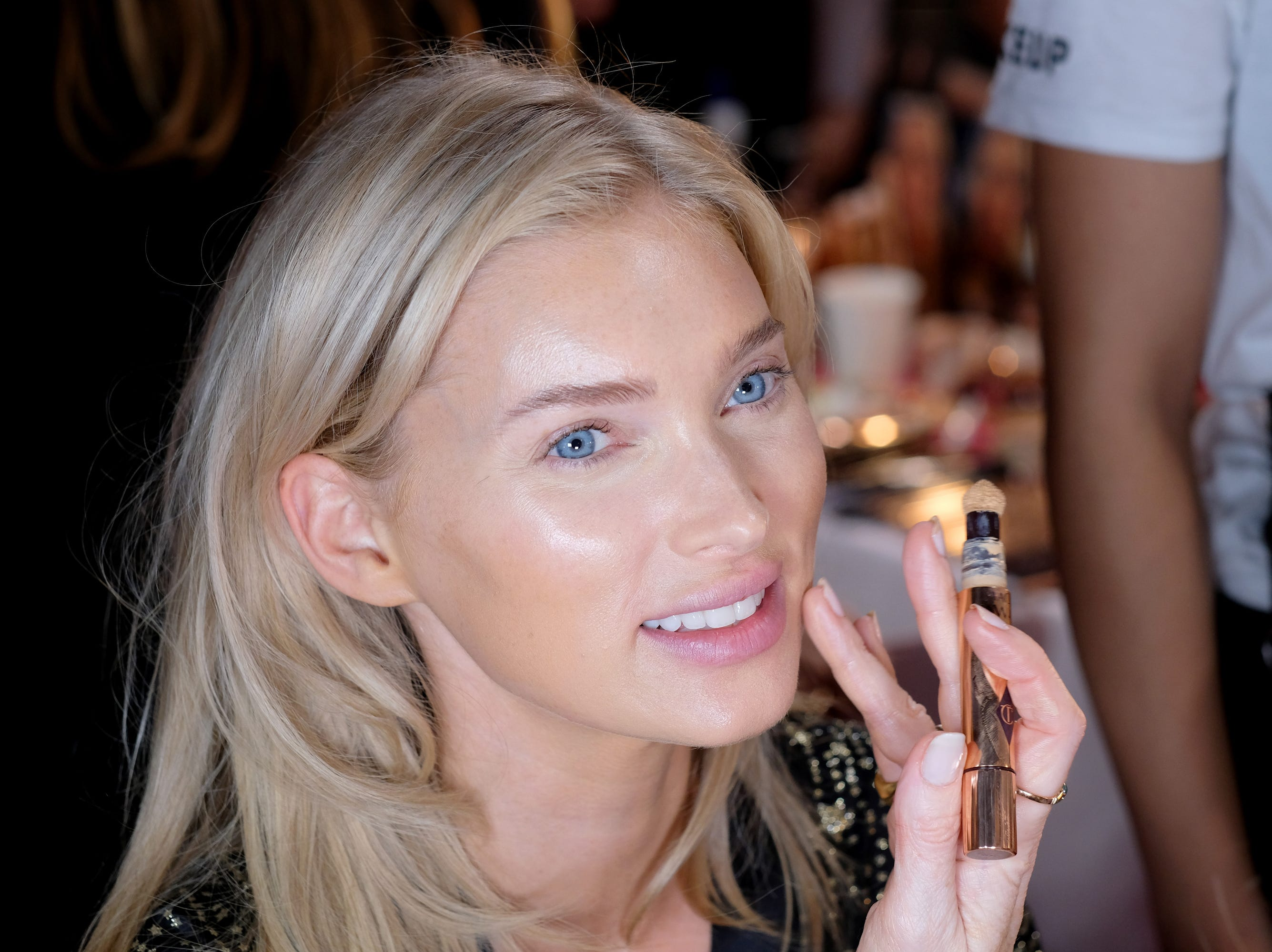 Elsa Hosk's has her makeup applied  backstage.