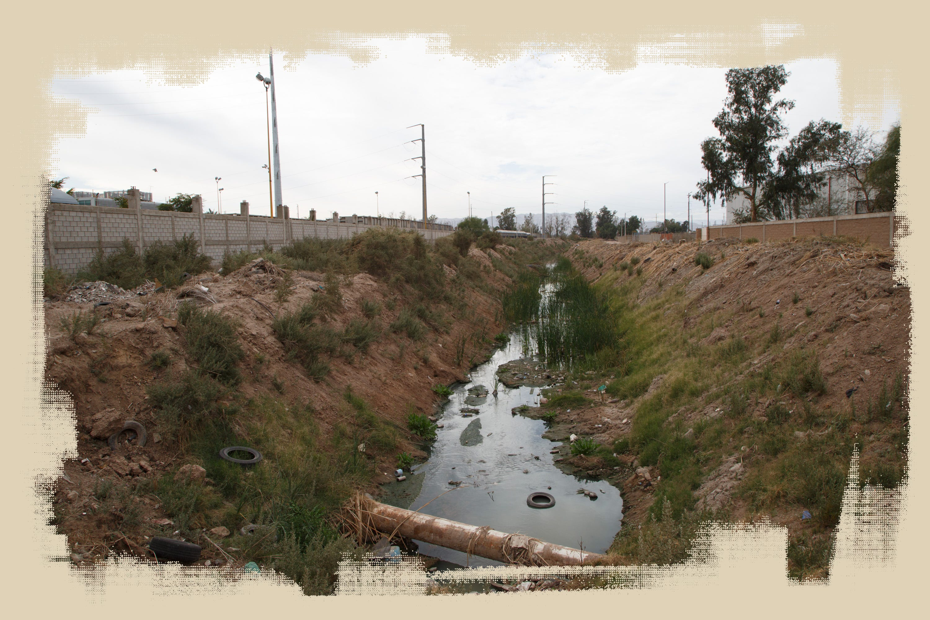 A ditch runs between the Vitro glass factory and a scrapyard in Mexicali. The city's ditches drain into the New River.