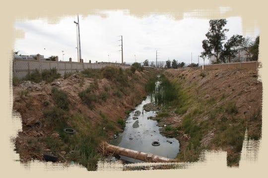 Una zanja corre entre la planta Vitro y un depósito de chatarra en Mexicali. Las zanjas de la ciudad desembocan en el río Nuevo.