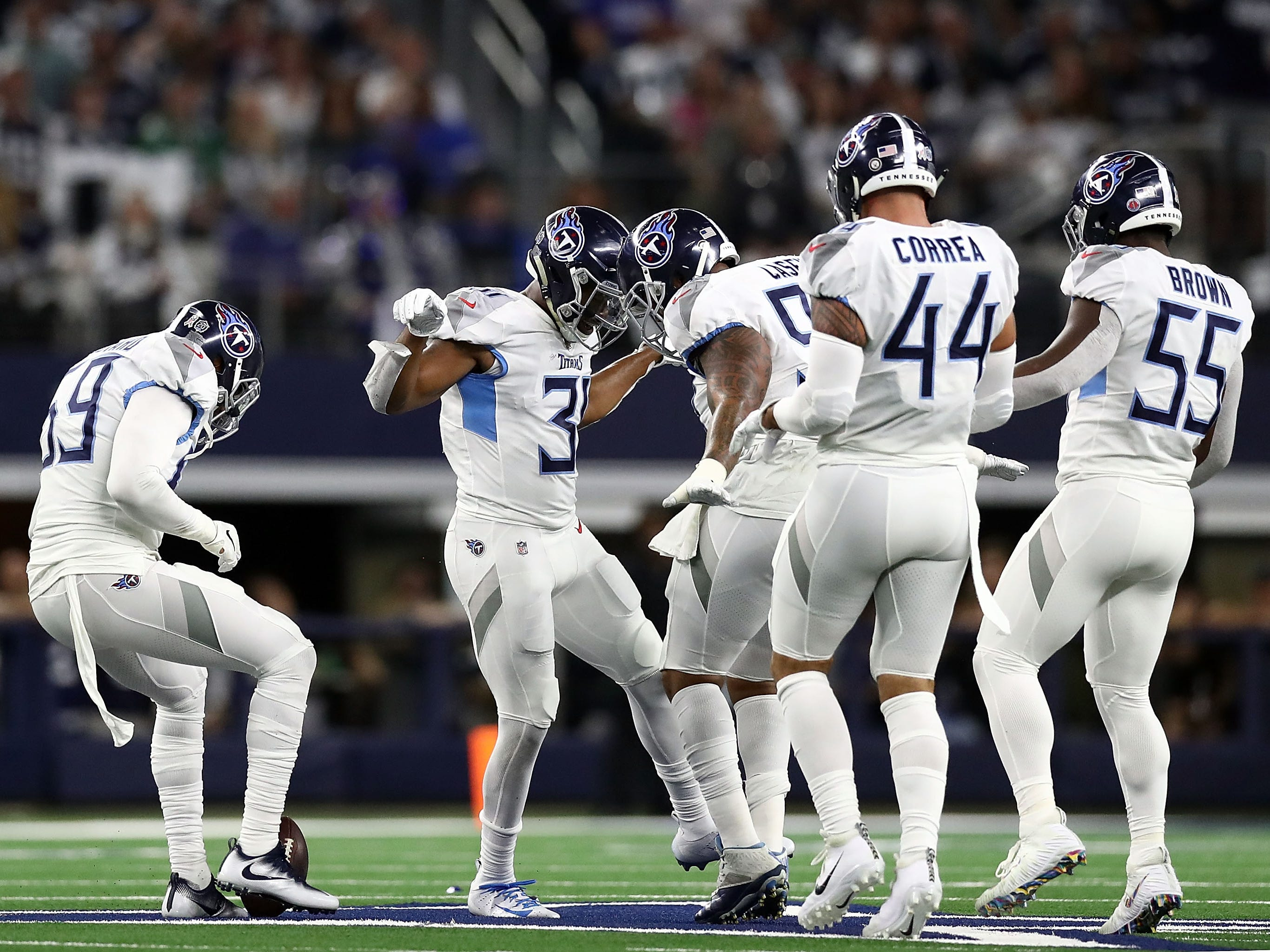 Tennessee Titans players celebrate a first quarter interception by Kevin Byard (31) on the Dallas Cowboys midfield star logo at AT&T Stadium. The Titans won the game, 28-14.