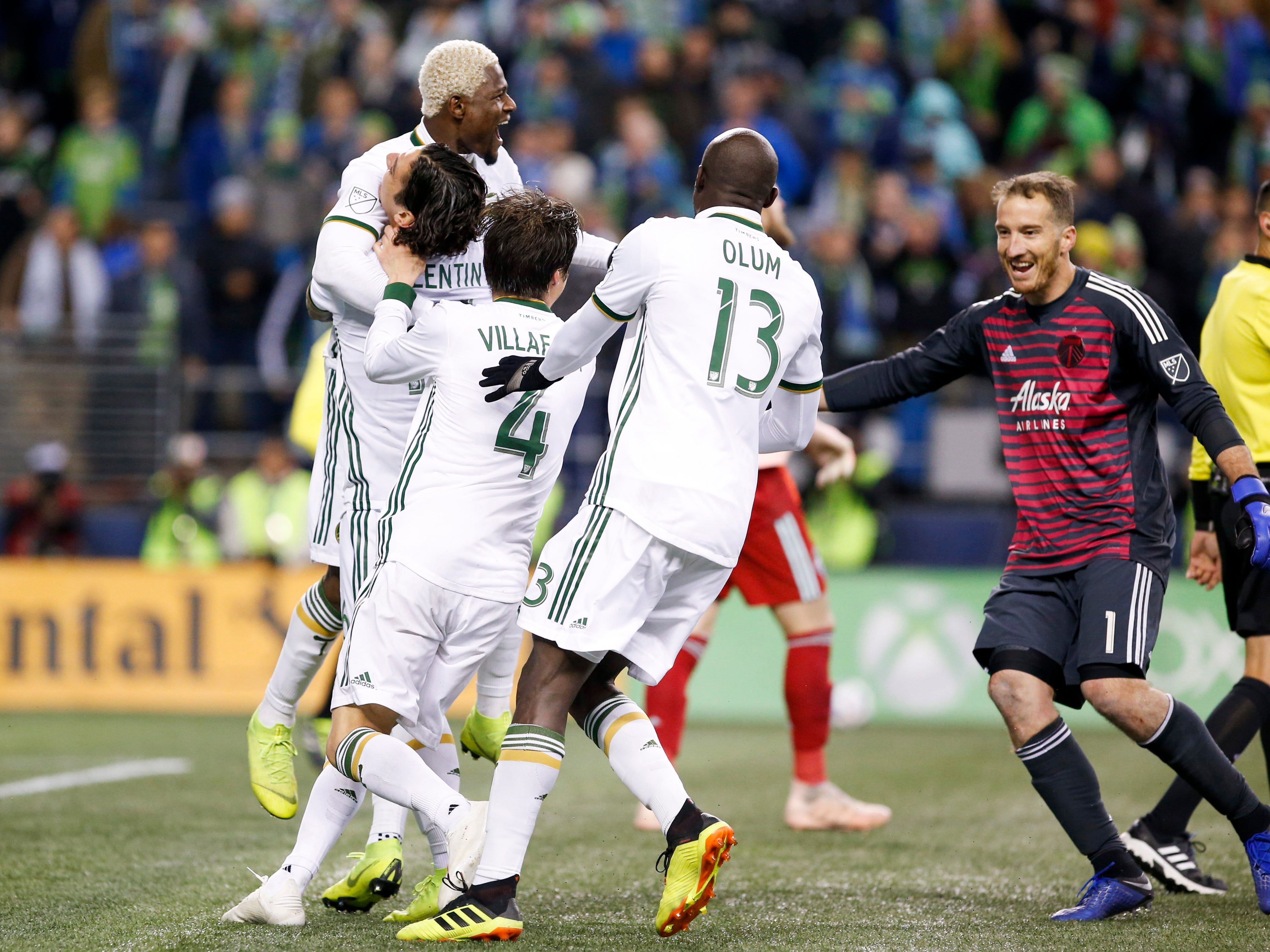 Portland Timbers forward Dairon Asprilla (left) celebrates with teammates including goalkeeper Jeff Attinella after winning a penalty shootout against the Seattle Sounders FC at CenturyLink Field.