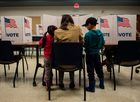 A woman and her children vote at a polling station in Fairfax County, Virginia, on Tuesday. Fairfax County saw votes for Democrats go from 59% in 2016 to 69% in 2018.