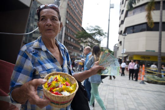 Elia Duran, 79, sells gum and her Venezuelan money on the streets of Medellin, Colombia on September 27, 2018. She fled from Venezuela six months ago, describing political turmoil and starvation. Now she struggles to get by in Colombia's biggest city and fears for the family she was forced to leave behind in her home country.
