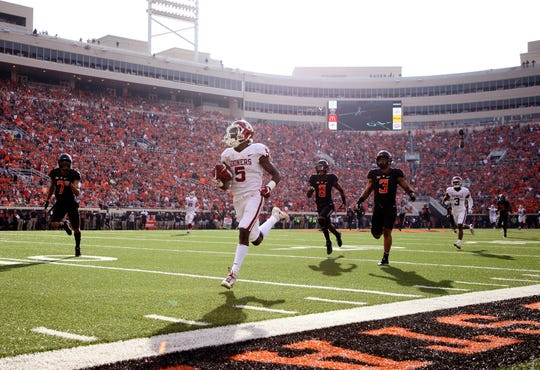 Oklahoma wide receiver Marquise Brown runs for a touchdown past Oklahoma State's defense during their game in 2017.