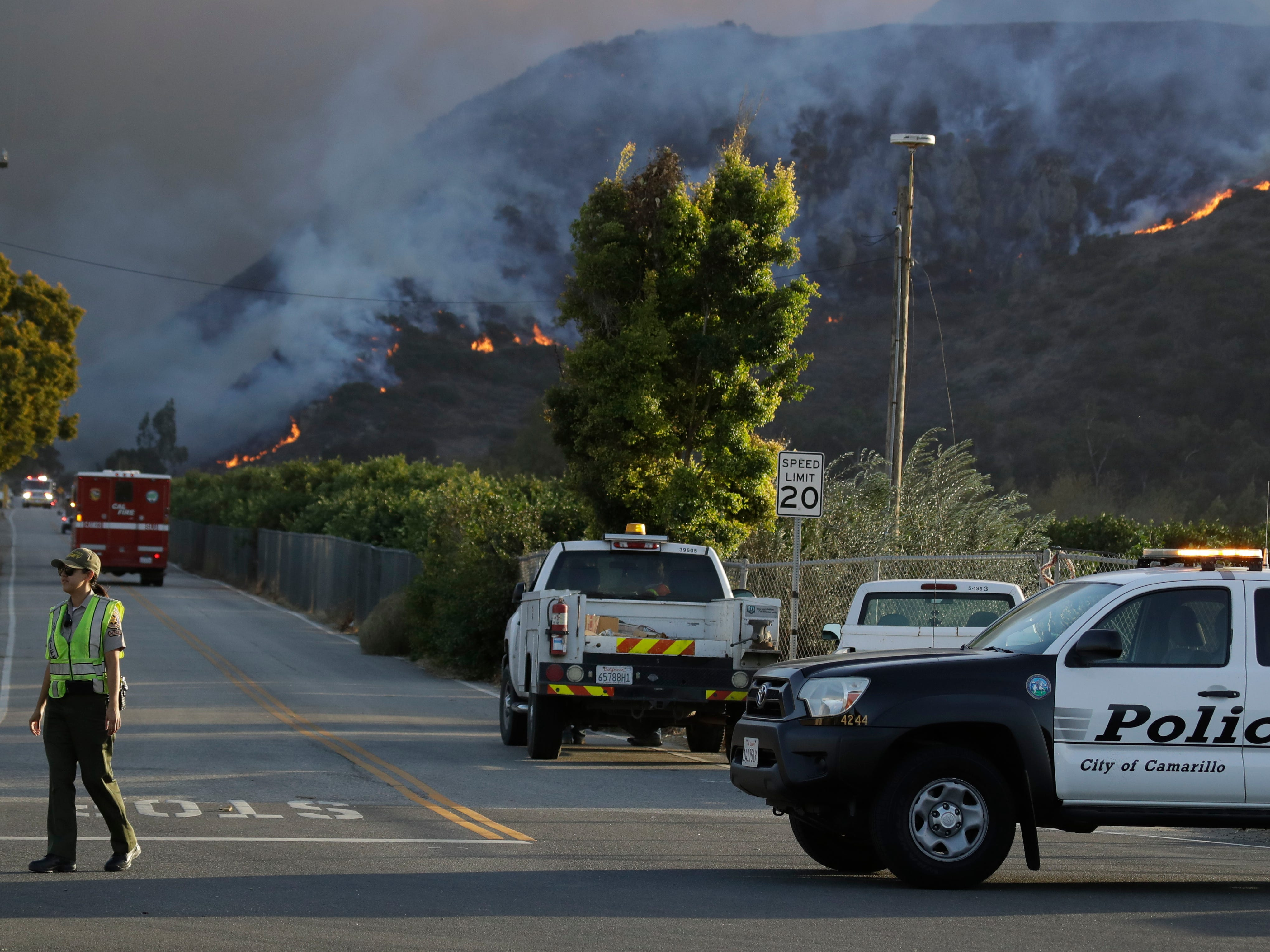 A police officer mans a checkpoint in front of an advancing wildfire Nov. 8, 2018, near Newbury Park, Calif.