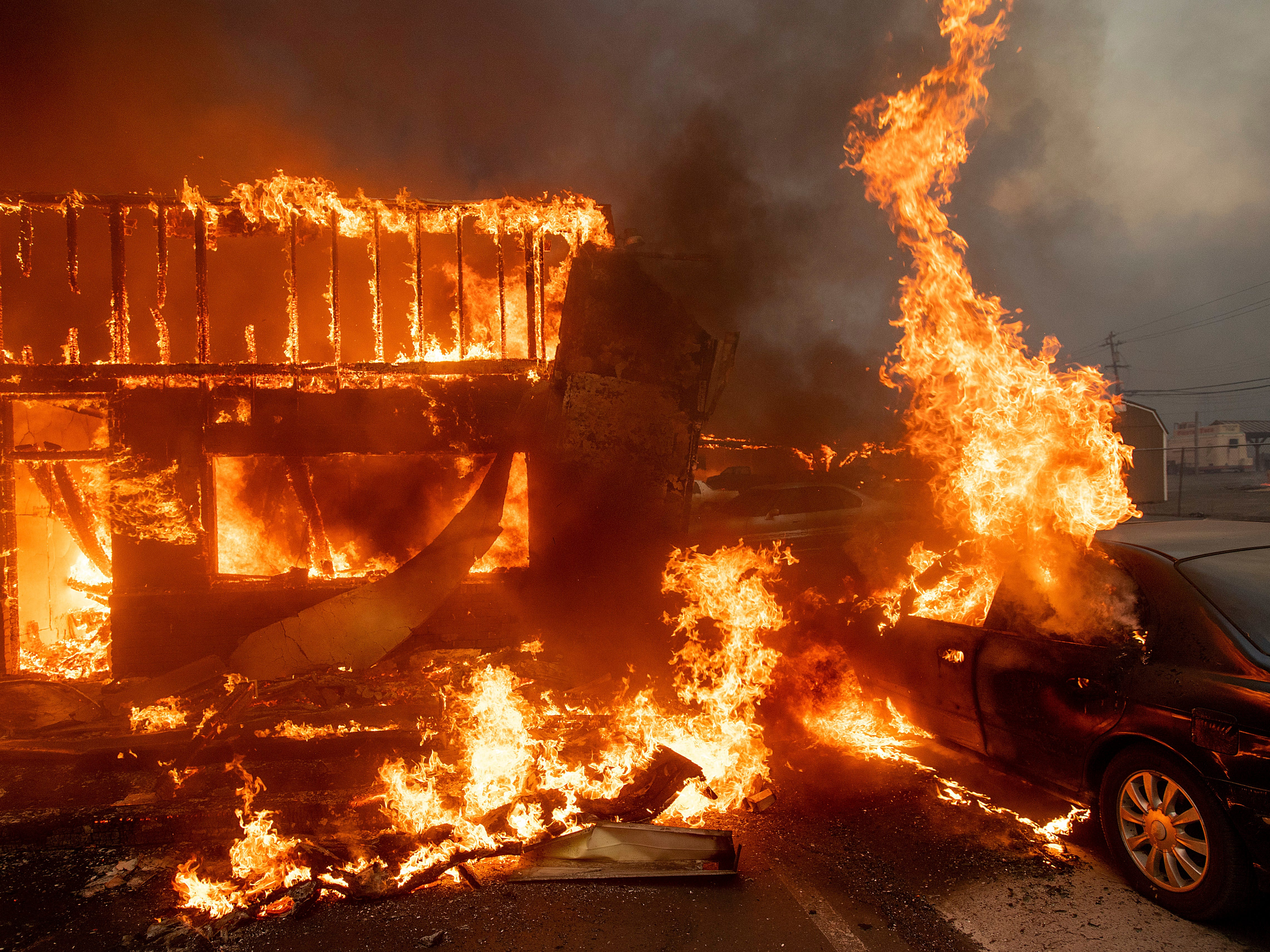 Flames consume a car and building as the Camp Fire tears through Paradise, Calif., on  Nov. 8, 2018.
