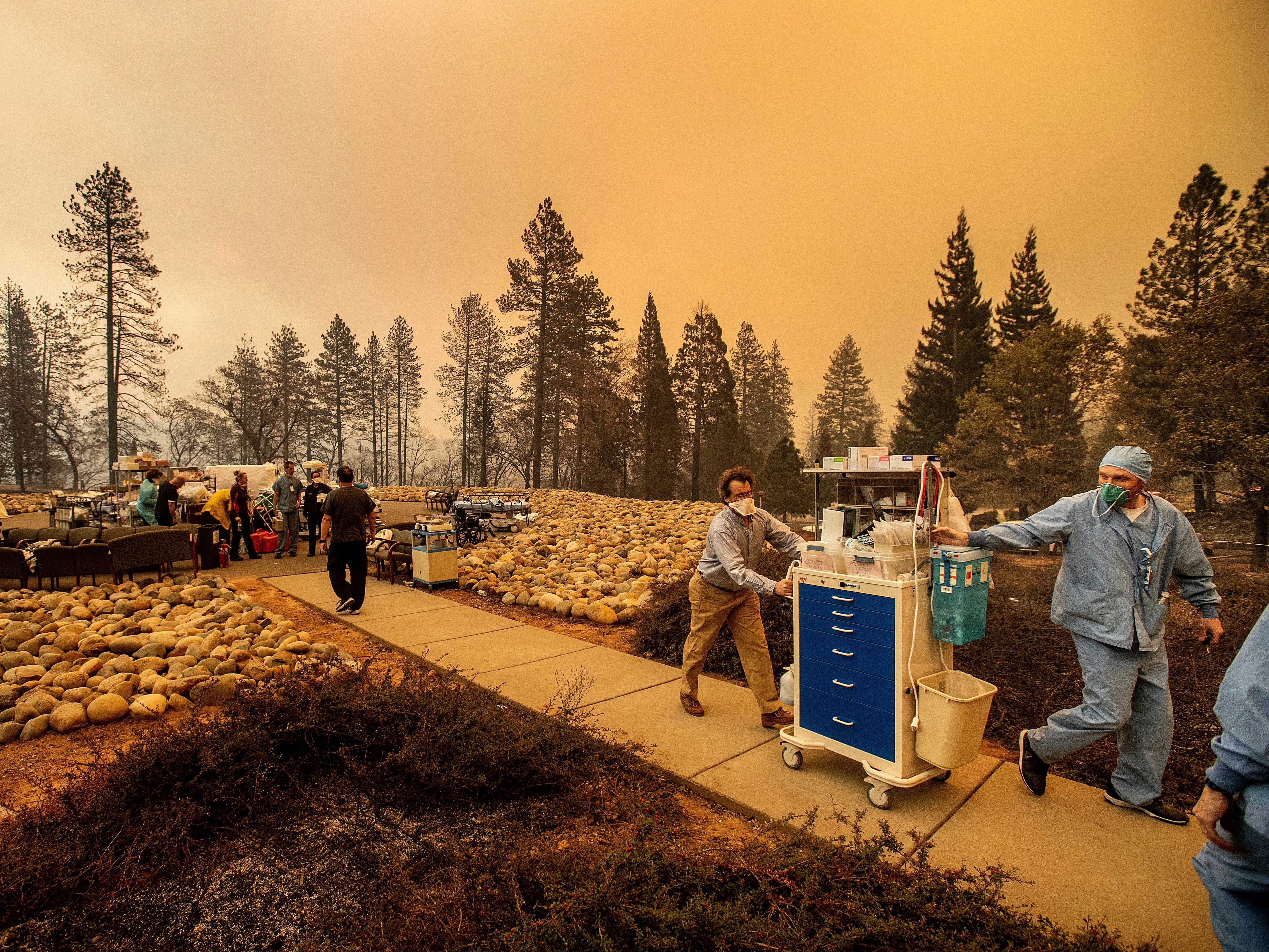 Medical workers move equipment from a makeshift emergency room while the Feather River Hospital burns as the Camp Fire rages through Paradise, Calif., on Nov. 8, 2018.