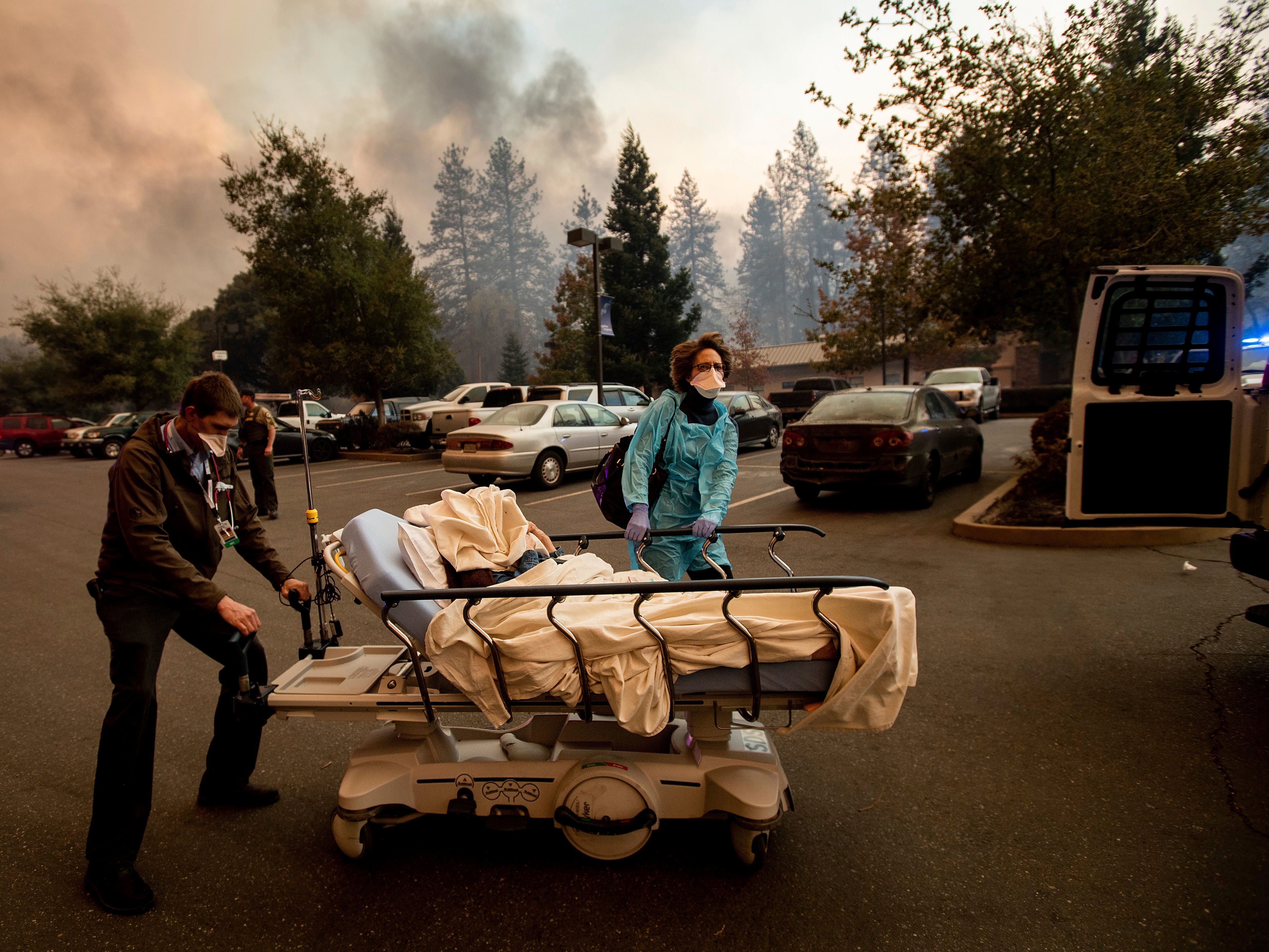 Medical personnel evacuate patients as the Feather River Hospital burns while the Camp Fire rages through Paradise, Calif., on Nov. 8, 2018.