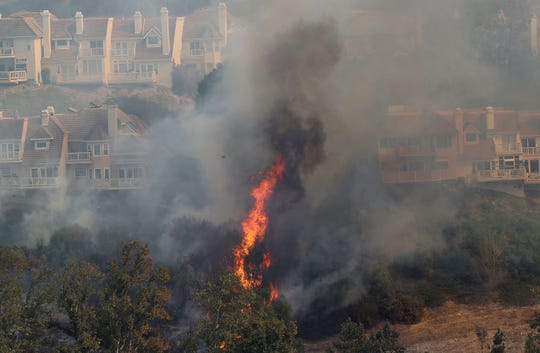 Flames from the Woolsey Fire threaten hillside homes in Westlake Village, Ca., on Friday.