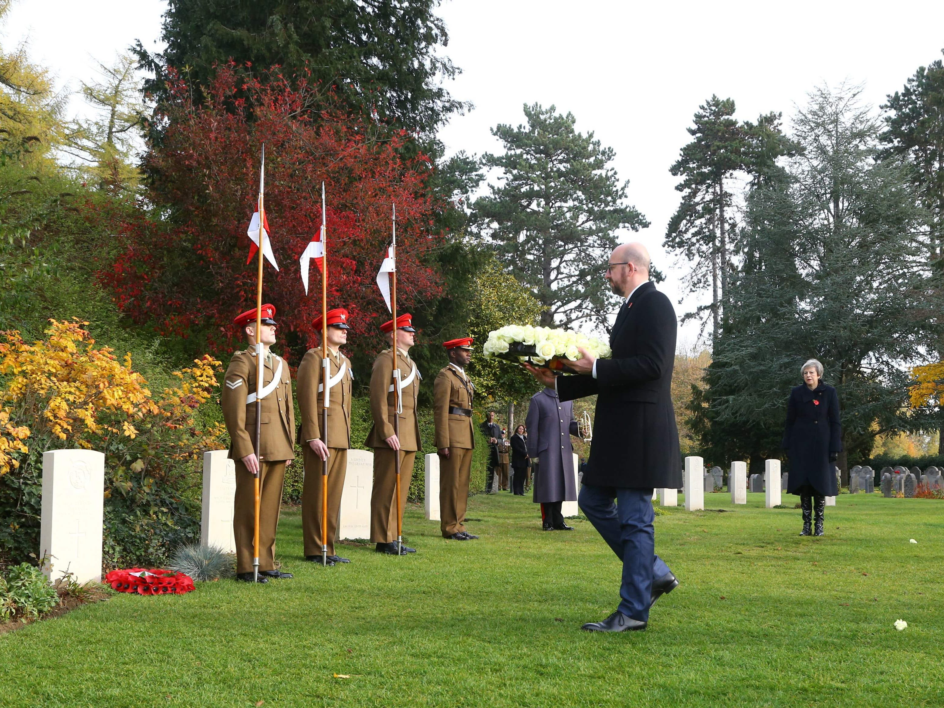 Britain's Prime Minister Theresa May (R) watches as Belgium's Prime Minister Charles Michel prepares to lay a wreath at the grave of George Ellison, the last British soldier to be killed before Armistice in 1918, at the St Symphorien Military Cemetery in Mons, Belgium, on November 9, 2018. - British Prime Minister Theresa May and French President Emmanuel Macron are set to commemorate their countries' shared sacrifice in the First World War on Friday and discuss the future of their post-Brexit relationship. The commemoration, just ahead of the 100th anniversary of the end of WWI, will be held at the Thiepval Memorial to the Missing of the Somme, in northern France, near the Belgian border. (Photo by Gareth Fuller / POOL / AFP)GARETH FULLER/AFP/Getty Images ORIG FILE ID: AFP_1AP3KM