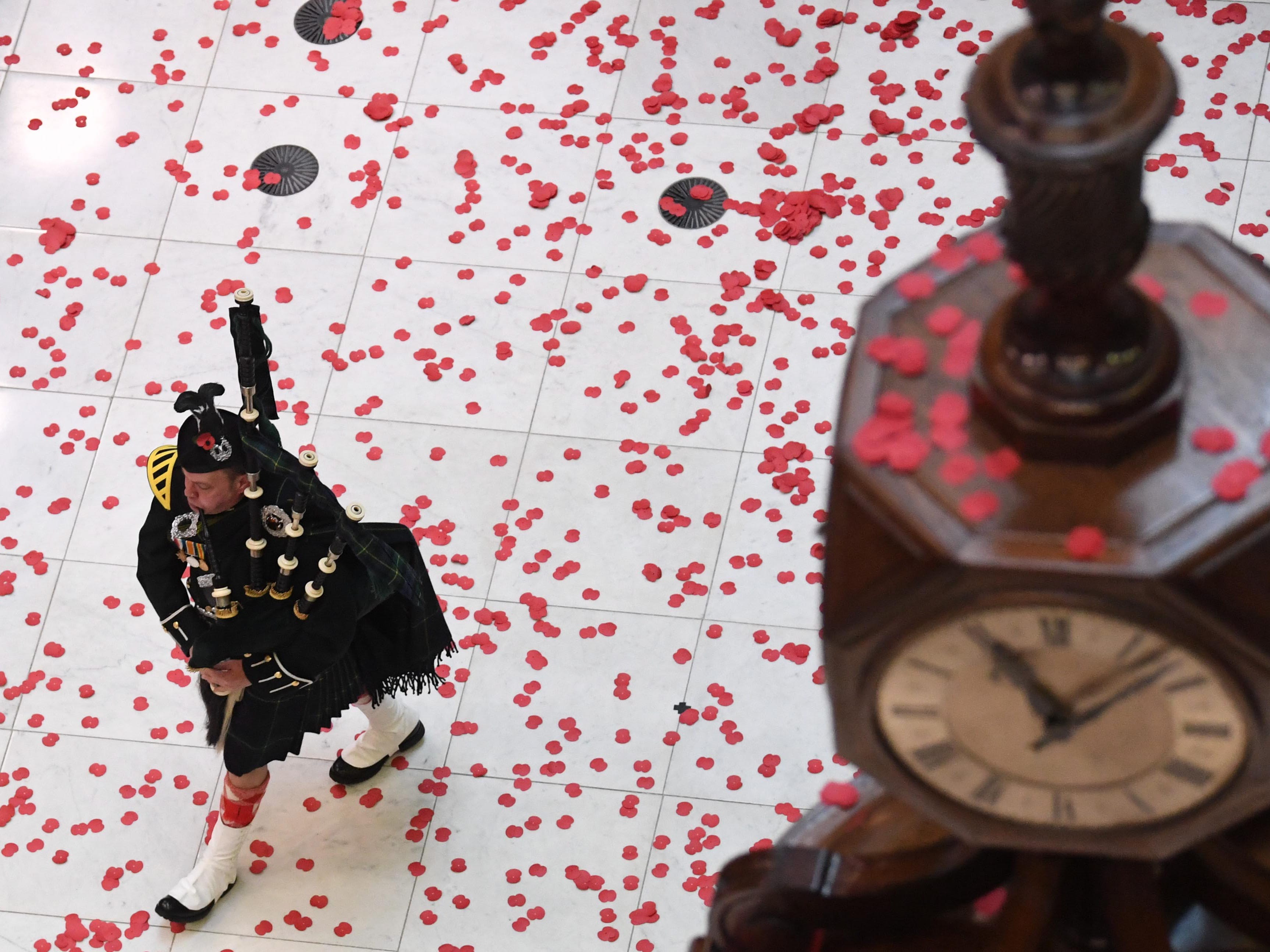 epa07153076 Poppies fall on a Scottish piper during the annual Remembrance Day Armistice commemoration service at Lloyds of London, in the City of London, Britain, 09 November 2018. The 11 November 2018 marks the 100th anniversary of the First World War Armistice with services taking place across the world to commemorate the occasion.  EPA-EFE/NEIL HALL ORG XMIT: NGH01