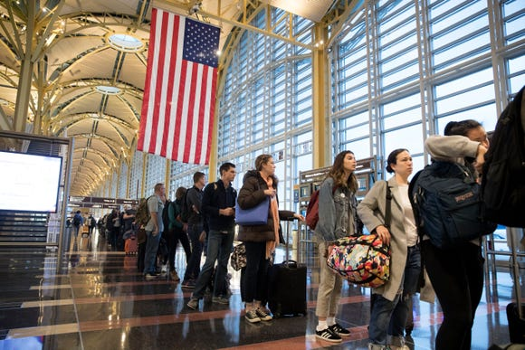 Travelers wait in line to go through security at Ronald Reagan Washington National Airport in Arlington, Virginia, on Nov. 22, 2017.