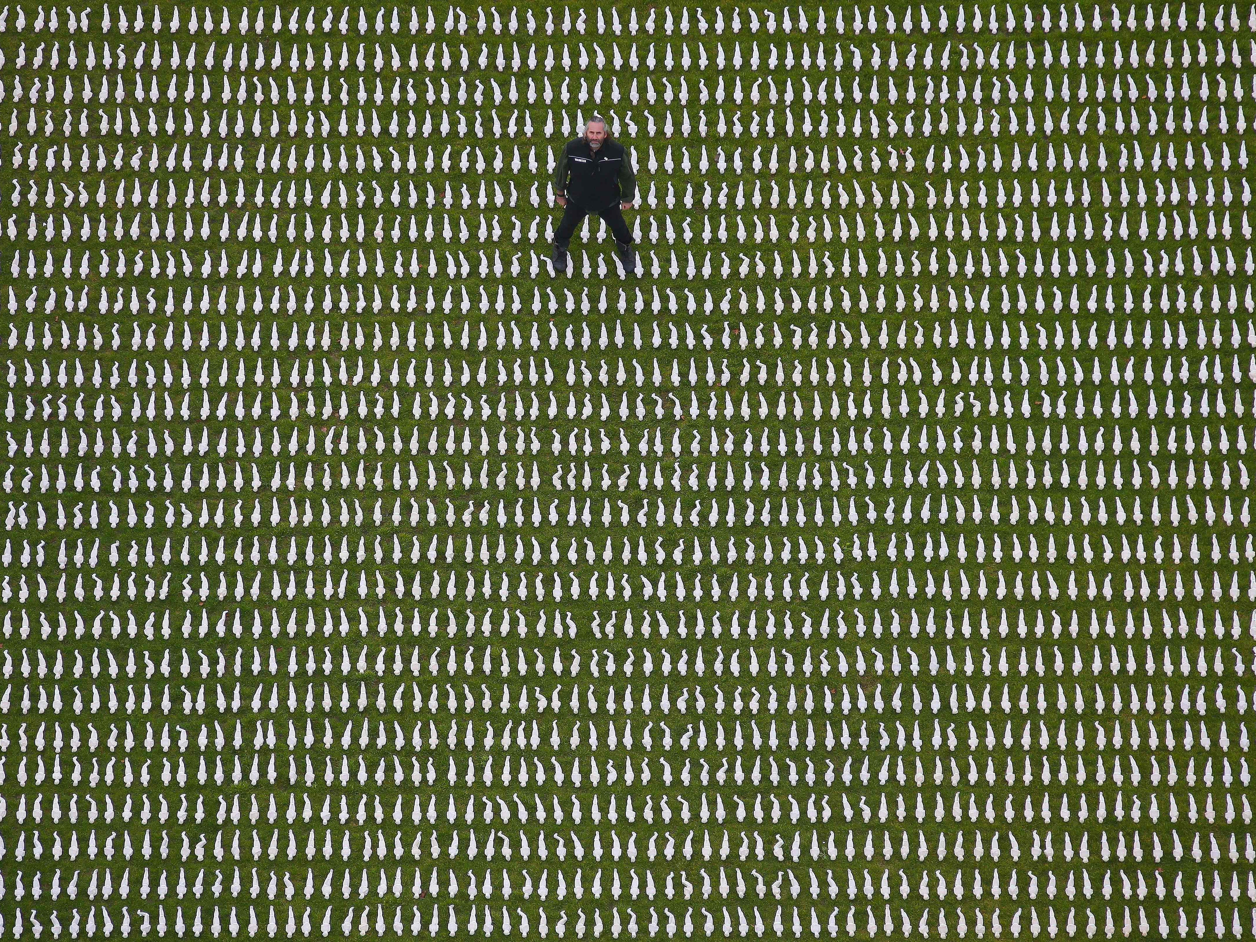 "British artist Rob Heard poses for a photograph amongst 72,396 shrouded figures, which form his installation ""Shrouds of the Somme"", laid out at the Queen Elizabeth Olympic Park in London on November 7, 2018, to represent Commonwealth servicemen who died at the Somme, and who have no known grave. - The 12 inch shrouded figures have been laid out by volunteers and members of the British Army's 1 Royal Anglian Regiment to mark the 100th anniversary of the end of the First World War. (Photo by Daniel LEAL-OLIVAS / AFP) / RESTRICTED TO EDITORIAL USE - MANDATORY MENTION OF THE ARTIST UPON PUBLICATION - TO ILLUSTRATE THE EVENT AS SPECIFIED IN THE CAPTIONDANIEL LEAL-OLIVAS/AFP/Getty Images ORIG FILE ID: AFP_1AN232"