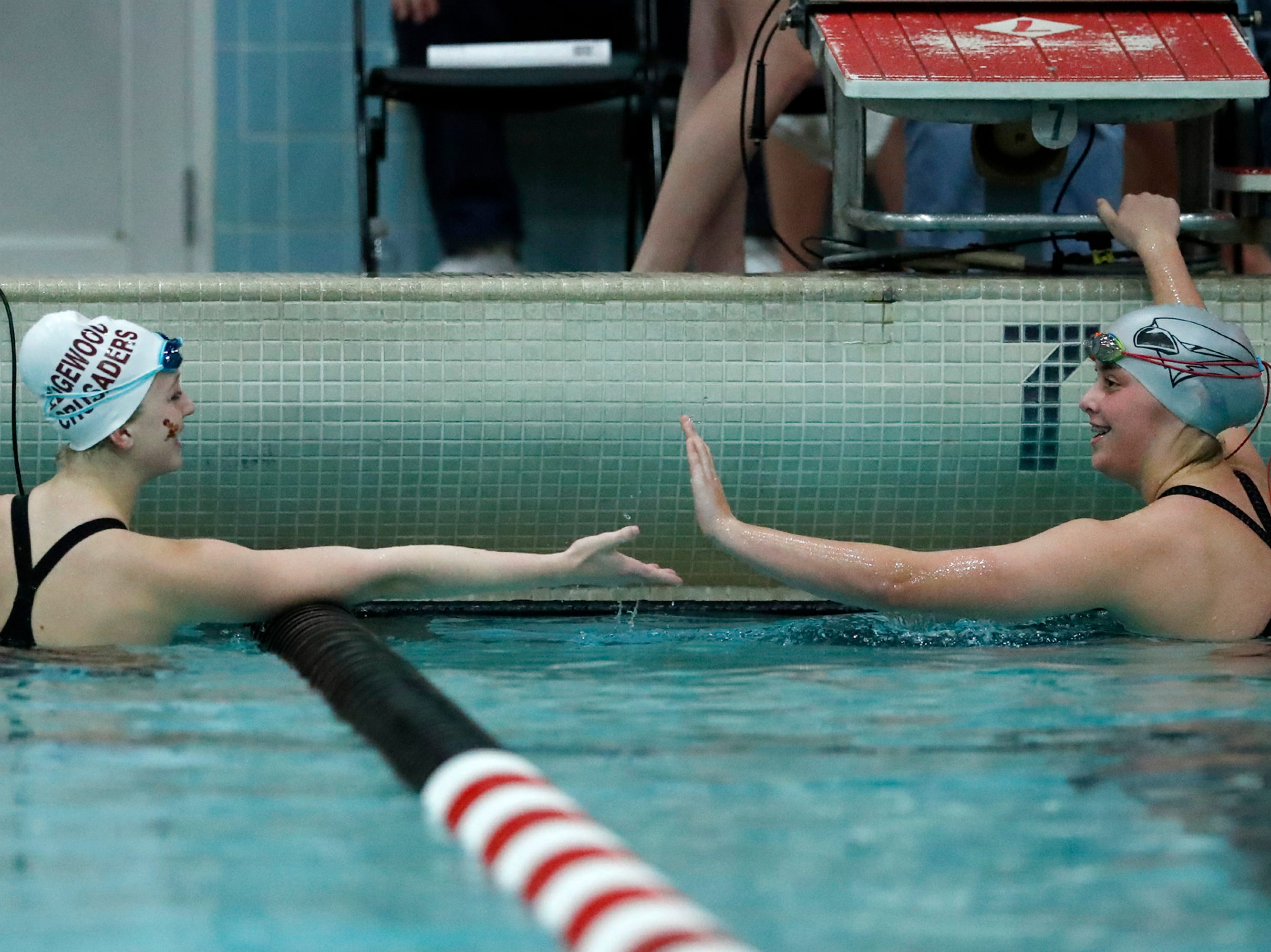 Edgewood's Issy Petersen shakes hands with Merrill's Claire Schultz after finishing the 50 yard freestyle during the WIAA Division 2 State Swimming and Diving meet Friday, Nov. 9, 2018, at the UW Natatorium in Madison, Wis.Danny Damiani/USA TODAY NETWORK-Wisconsin
