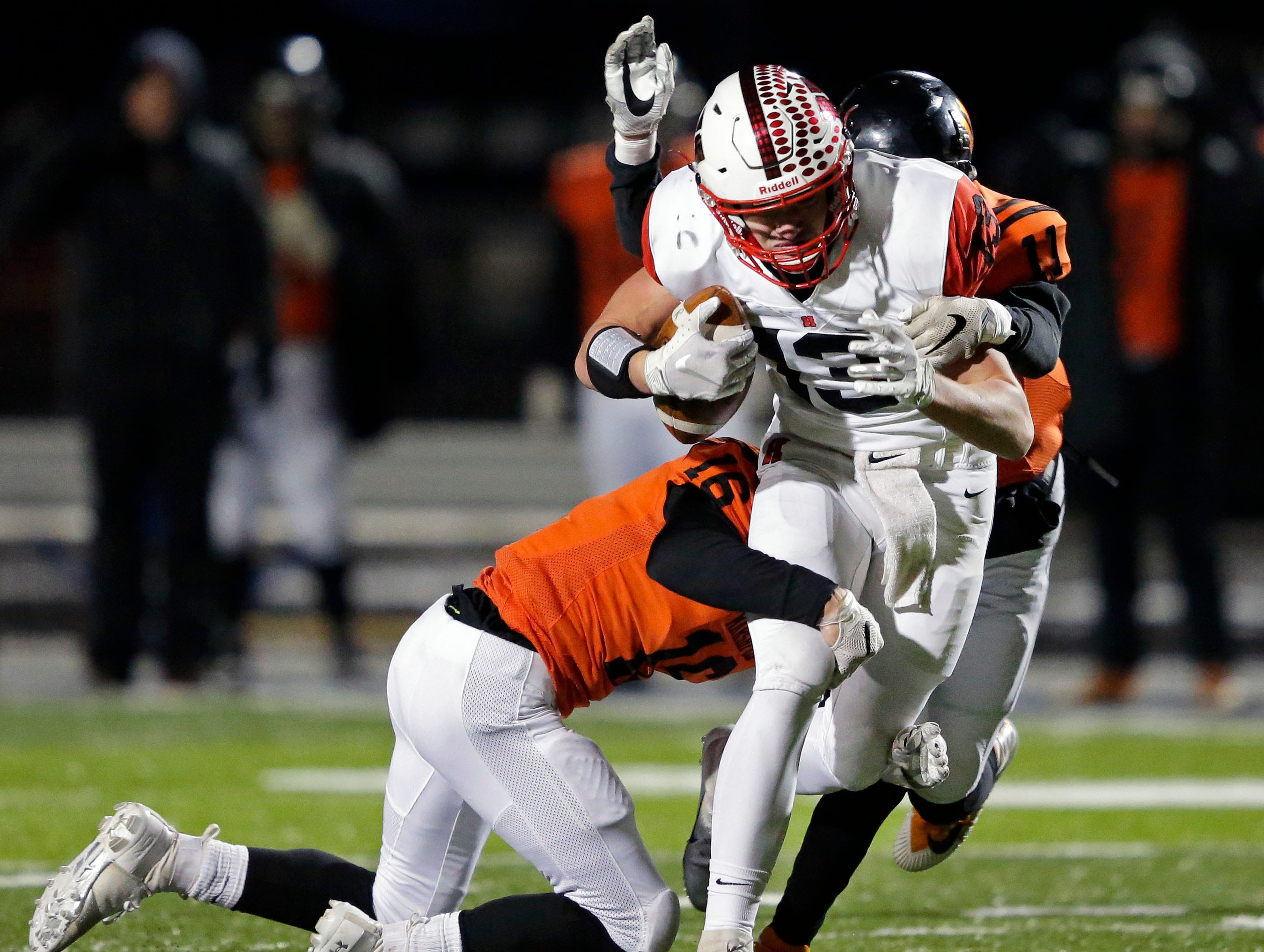 Howie Newbauer of Homestead is tackled by Bently Schwanebeck-Ostermann (16) and Joey Goettl (11) of Marshfield in a WIAA Division 2 state semifinal football game Friday, November 9, 2018, at Calder Stadium in Menasha, Wis.Ron Page/USA TODAY NETWORK-Wisconsin