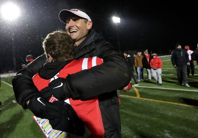 Kimberly High School head coach Steve Jones hugs Drew Lechnir after a 22-21 overtime victory against Fond du Lac High School in the WIAA Division 1 state semifinal football game at Titan Stadium in Oshkosh.
