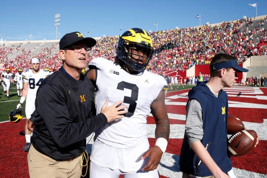 Jim Harbaugh walks off the field with Rashan Gary, after a win at Indiana in 2017.