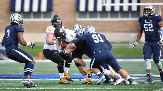 Monmouth defenders, including defensive tackle Kurt Aumer (91), tackle Kennesaw State quarterback Chandler Burks in the first half on Saturday at Kessler Stadium in West Long Branch.