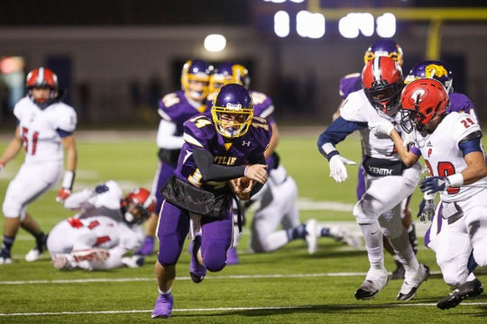 Wylie quarterback Jaxon Hansen runs the ball as a pair of Plainview defenders close in. Hansen scored a touchdown but his team fell 22-19 in the season finale for both teams.