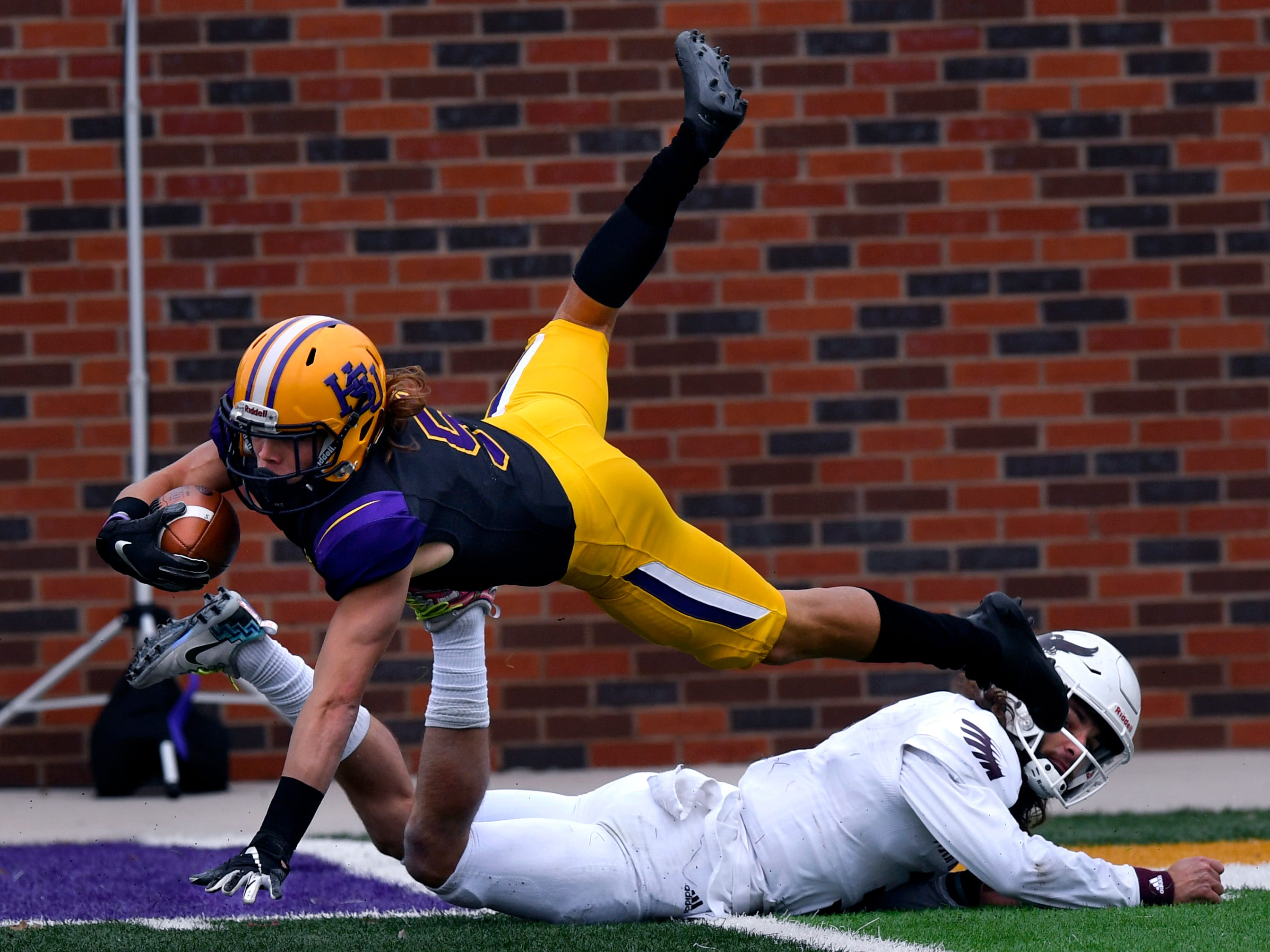 Hardin-Simmons wide receiver Reese Childress dives after being tackled by McMurry quarterback Kevin Hurley, jr. during Saturday's crosstown game at HSU Nov. 10, 2018. Final score was 83-6, HSU.