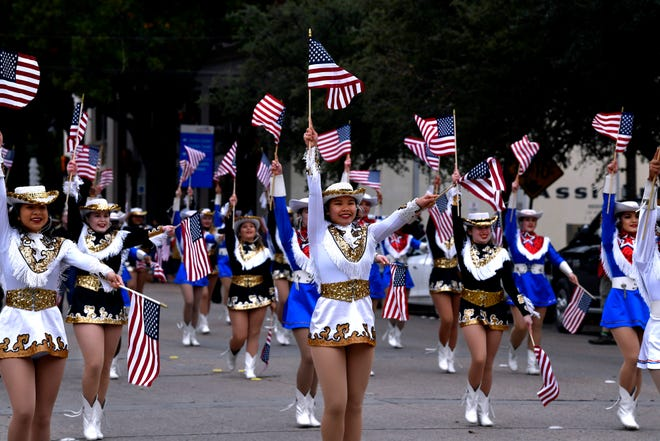 The combined dance teams from Abilene and Cooper high schools march during Saturday's Veterans Day parade in downtown Abilene. Despite a chilly day, attendees cheered their heroes.
