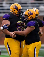 Hardin-Simmons offensive lineman Bryant Buzzard (65) is congratulated for his touchdown by Juan Martinez during the Cowboys' game against McMurry University. Buzzard bulldozed the final yard into the end zone in the second quarter.