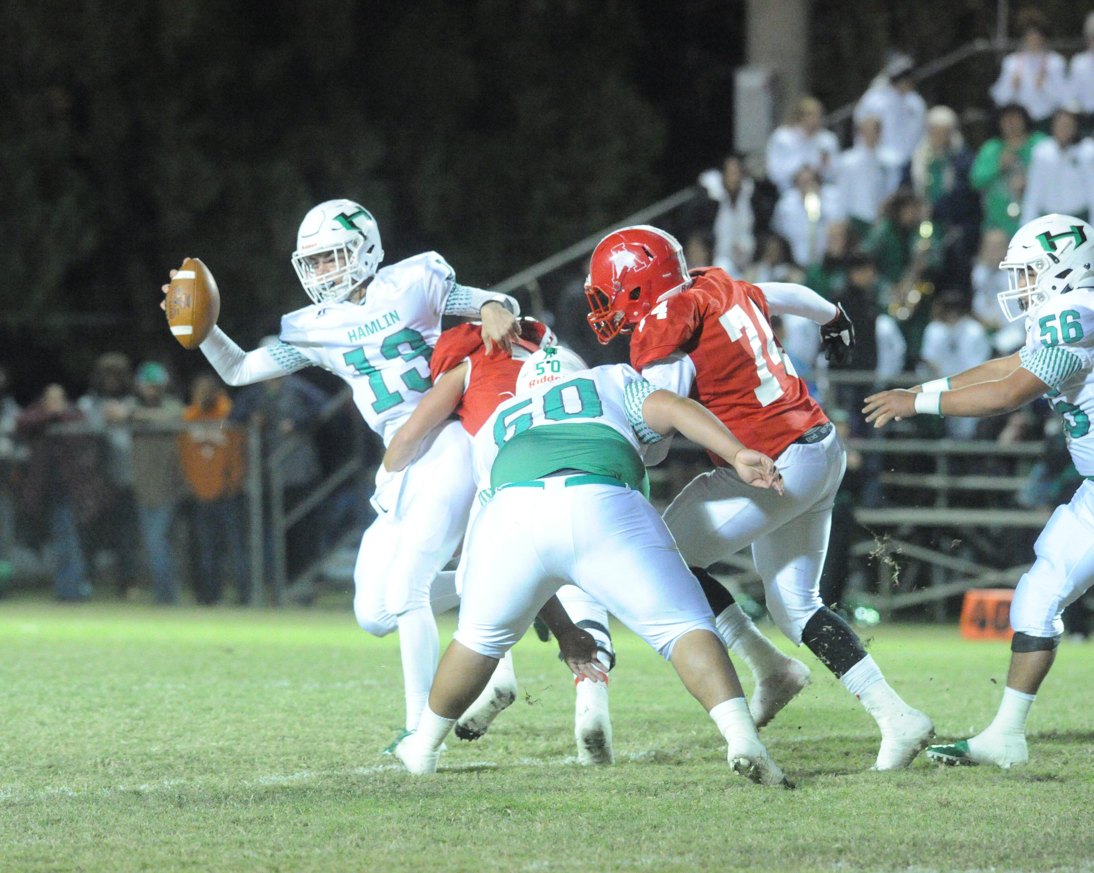 Hamlin sophomore quarterback Braydin Warner (13) is sacked by Albany's Payne Hebel as Coby Knight (74) closes in Friday night.